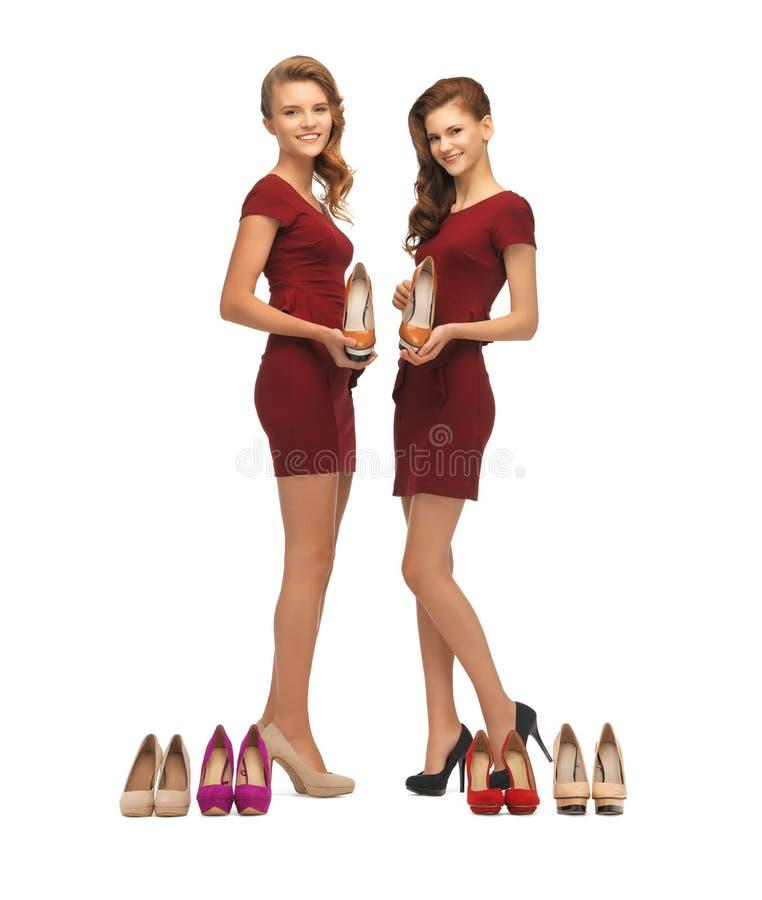 Zwei reizende Jugendlichen in den roten Kleidern mit Schuhen lizenzfreies stockbild