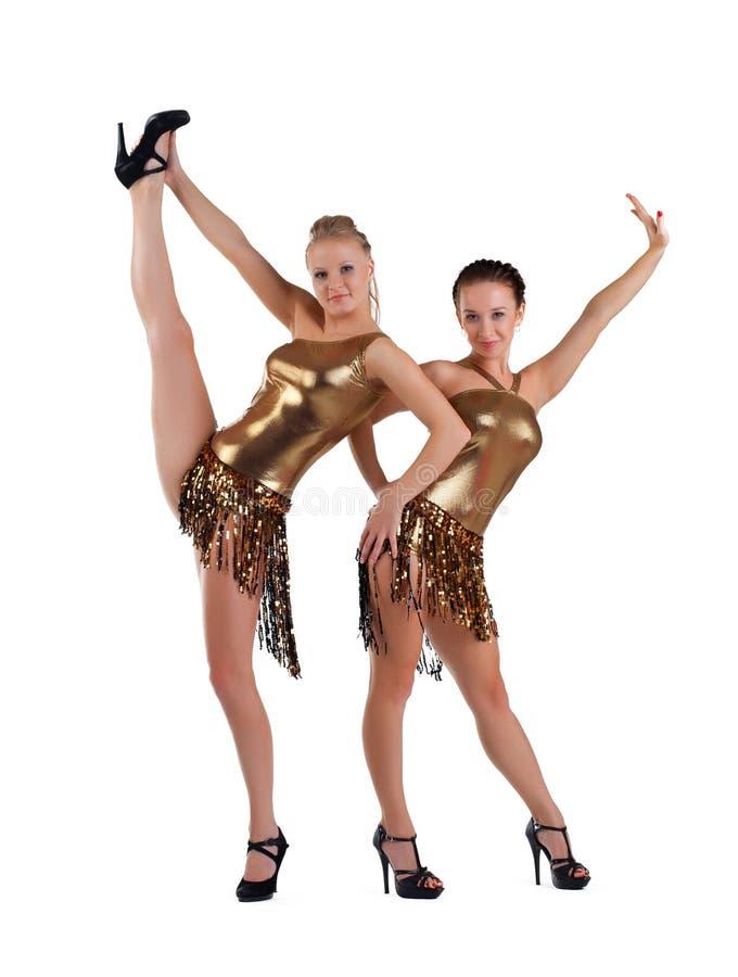 Zwei reizvolle Frauen, die im Goldgo-go Kostüm aufwerfen lizenzfreies stockfoto