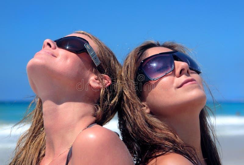 Zwei reizvolle junge Frauen, die auf einem Sandy-Strand ein Sonnenbad nehmen lizenzfreie stockbilder