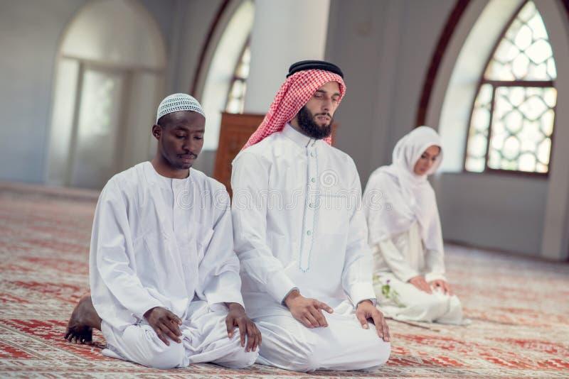 Zwei religiöse junge Leute, die innerhalb der Moschee beten islamisch stockfotos