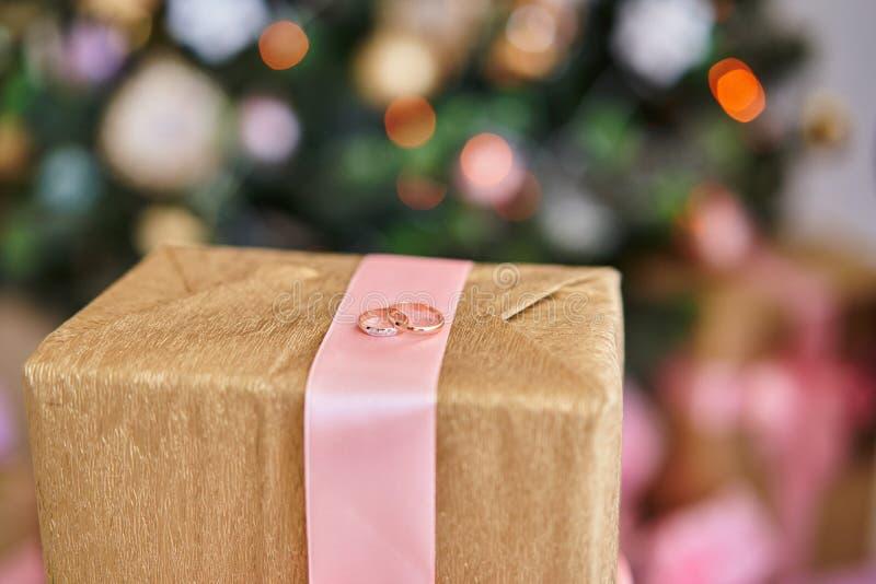 Zwei Ringe auf einer Geschenkbox auf dem Hintergrund des Weihnachtsbaums lizenzfreies stockbild