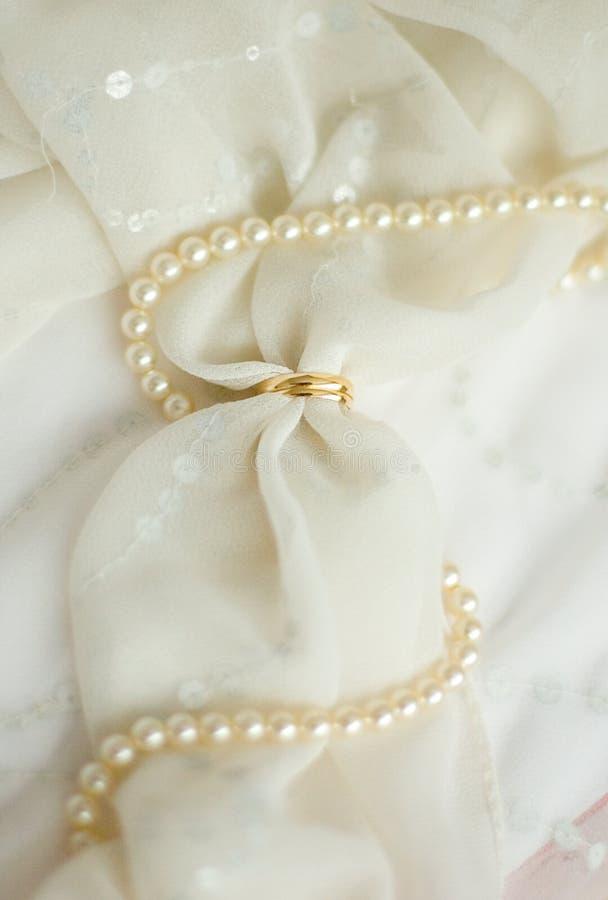 Zwei Ringe der goldenen Hochzeit auf Brautschleier lizenzfreie stockfotos
