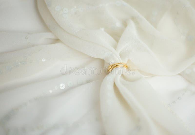 Zwei Ringe der goldenen Hochzeit mit Brautschleier stockbild