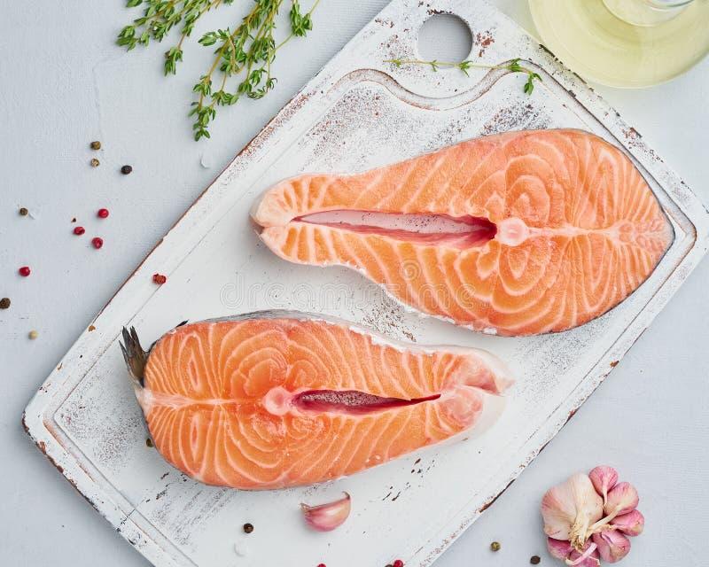 Zwei rohe Lachssteaks, Fischfilet, große geschnittene Teile auf hackendem Brett auf einer weißen Tabelle Beschneidungspfad einges stockbild