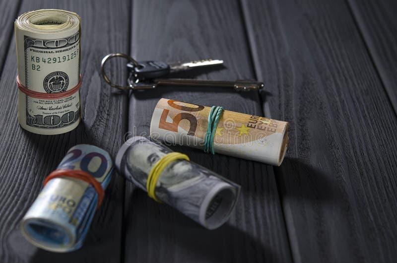 Zwei Rollen von Hundertdollar-Rechnungen, eine Fünfzigrollenrolle, eine ZwanzigEuro-Rolle gebunden mit Gummibändern auf einem sch stockfoto