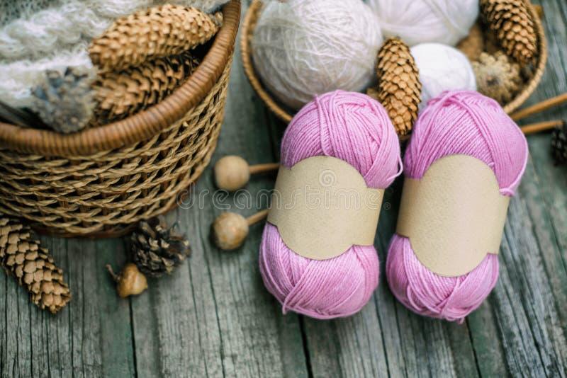 Zwei rosa Bälle von Wollfaden mit den leeren Aufklebern, die auf hölzernem Schreibtisch der Weinlese mit Stricknadeln und Korb li lizenzfreie stockbilder