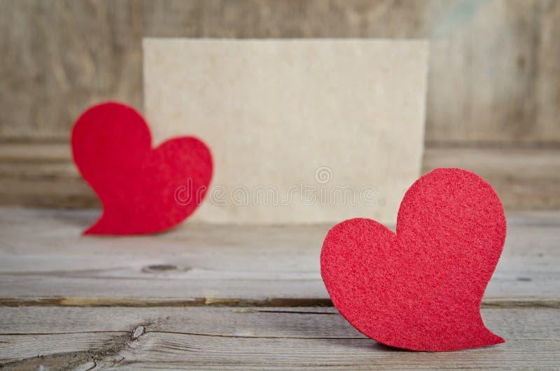 Zwei rote Gewebeherzen auf einem hölzernen Brett lizenzfreies stockfoto