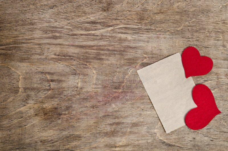 Zwei rote Gewebeherzen mit Blatt Papier stockbild