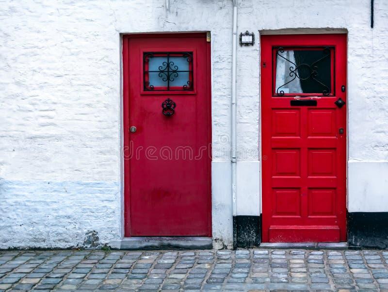 Zwei rote hölzerne Haustüren in der weißen Backsteinmauer lizenzfreie stockfotografie