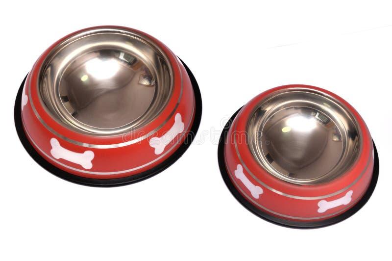 Zwei rote Haustierfressnäpfe mit weißem Hundeknochendrucken lizenzfreie stockbilder