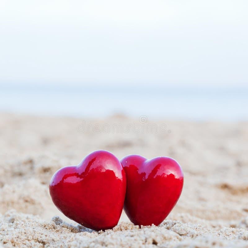 Zwei rote Herzen auf dem Strand, der Liebe symbolisiert stockfotos