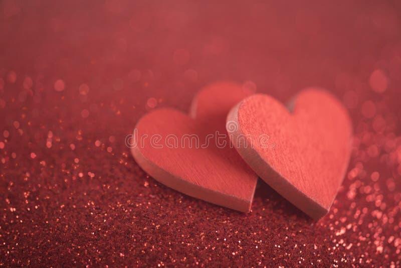 Zwei rote Herzen auf Funkelnhintergrund lizenzfreie stockfotos
