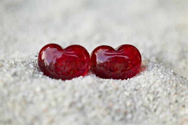 Zwei rote Herzen im Sand stockfotos