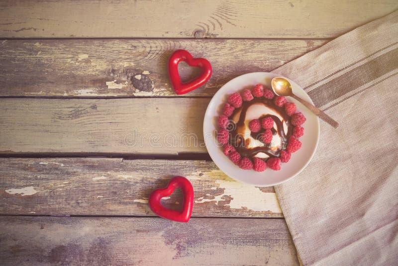 Zwei rote Herzen und italienischer Nachtisch panna Cotta mit frischem Himbeer- und Schokoladensirup stockfotos