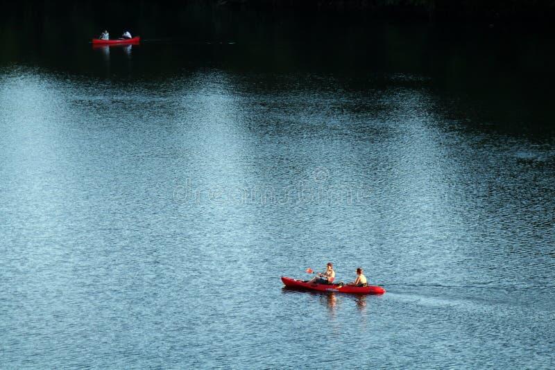 Zwei rote Kajaks, die helles und dunkles Wasser vom Colorado steuern, wie von der Kongressbrücke in Austin gesehen stockfotos