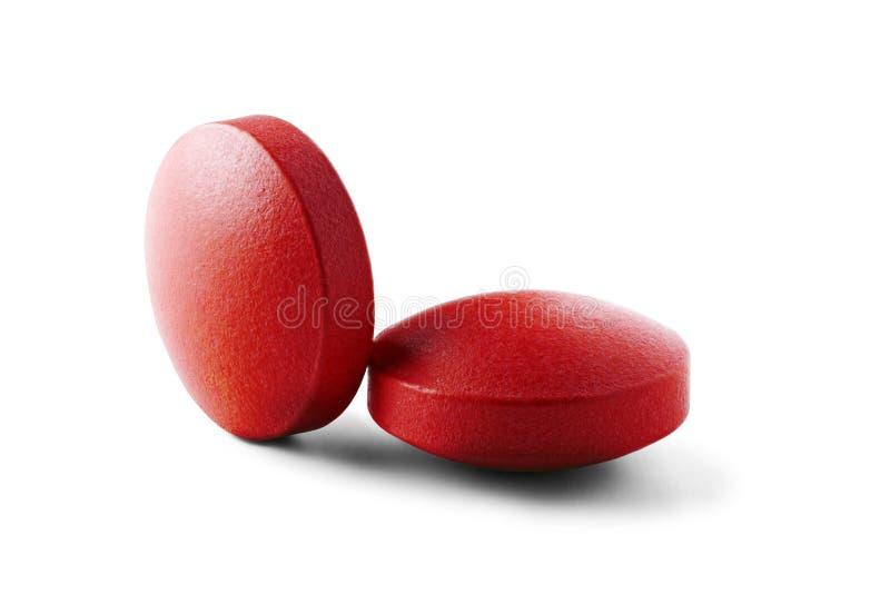 Zwei rote medizinische Pillen mit Schatten auf lokalisiertem weißem Hintergrund Pillen mit runder Form stockfotografie