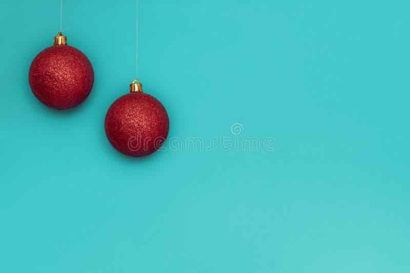 Zwei rote Weihnachtsbälle gegen grönländischen Hintergrund Kopieren von Leerzeichen auf der rechten Seite stockfoto