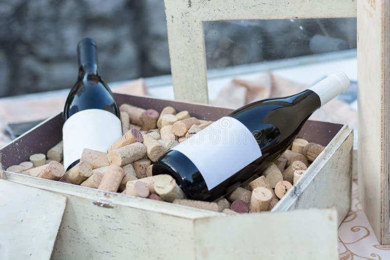Zwei Rotweinflaschen in der alten Holzkiste voll mit Korken stockfoto