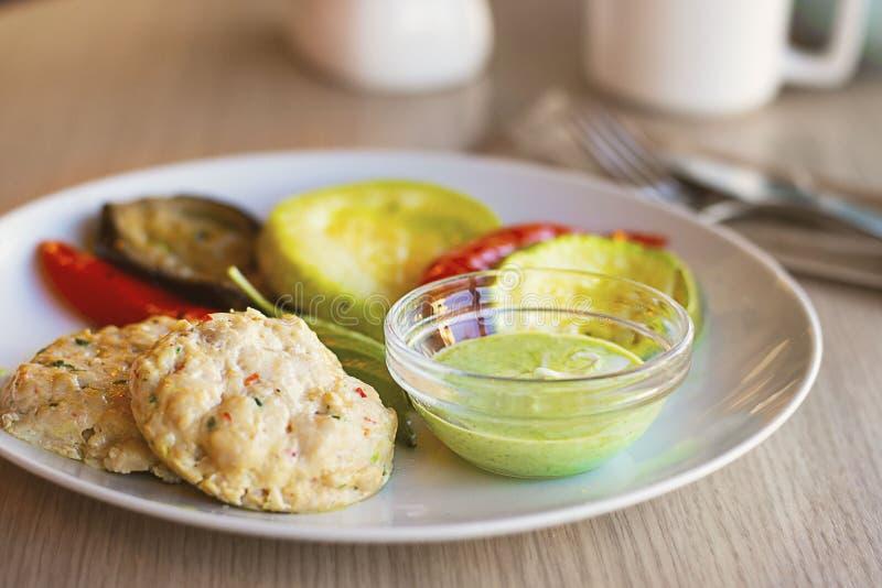 Zwei runde Hiebe gemacht von gehacktem Truthahn mit grüner Soße und gegrilltem Gemüse auf weißer Platte auf dem Holztisch herein lizenzfreie stockfotos