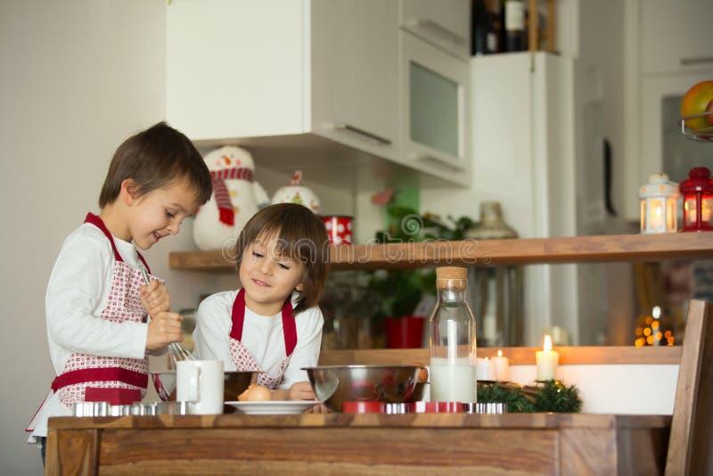 Zwei süße Kinder, Jungenbrüder, Lebkuchenplätzchen zubereitend stockbilder