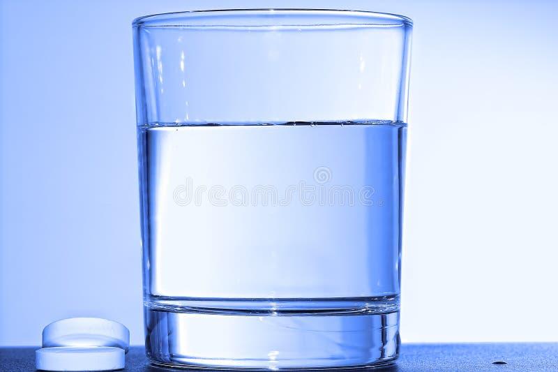 Zwei schäumende Tabletten und Glas mit Wasser lizenzfreie stockbilder
