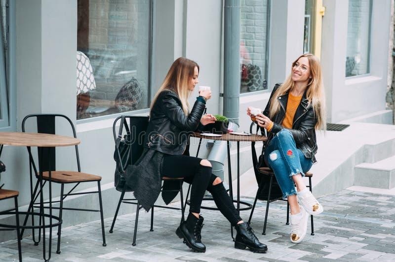 Zwei schöne attraktive stilvolle Frauen sind das Sitzen im Freien in Café trinkendem coffe und Tee großen Tag sprechend und genie stockbilder