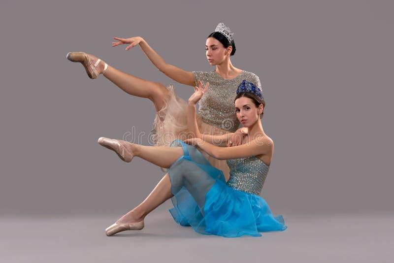 Zwei schöne Ballerinen, die im Studio und in der Aufstellung sitzen stockbilder
