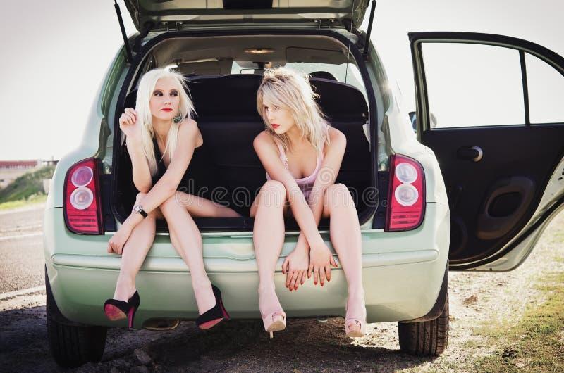 Zwei schöne blonde Mädchen, die im Stamm des defekten Autos sitzen lizenzfreie stockfotos