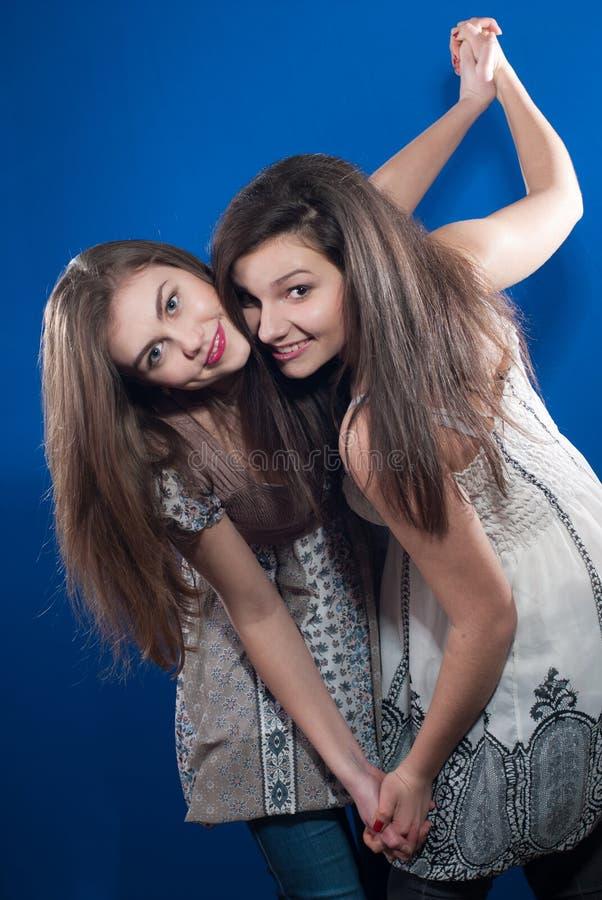 Zwei schöne Freunde der jungen Frauen, die zusammen tanzen stockbilder