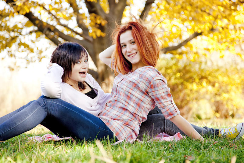 Zwei schöne Freundinnen am Herbstpark lizenzfreie stockfotos