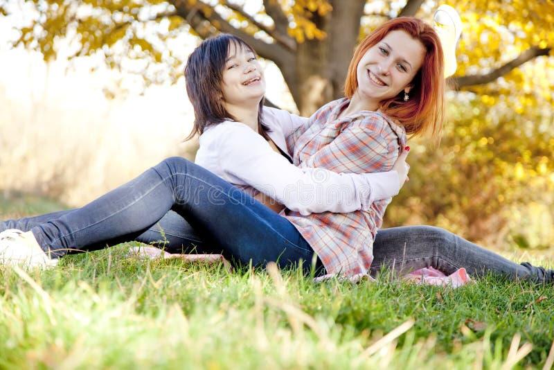 Zwei schöne Freundinnen am Herbstpark lizenzfreies stockfoto