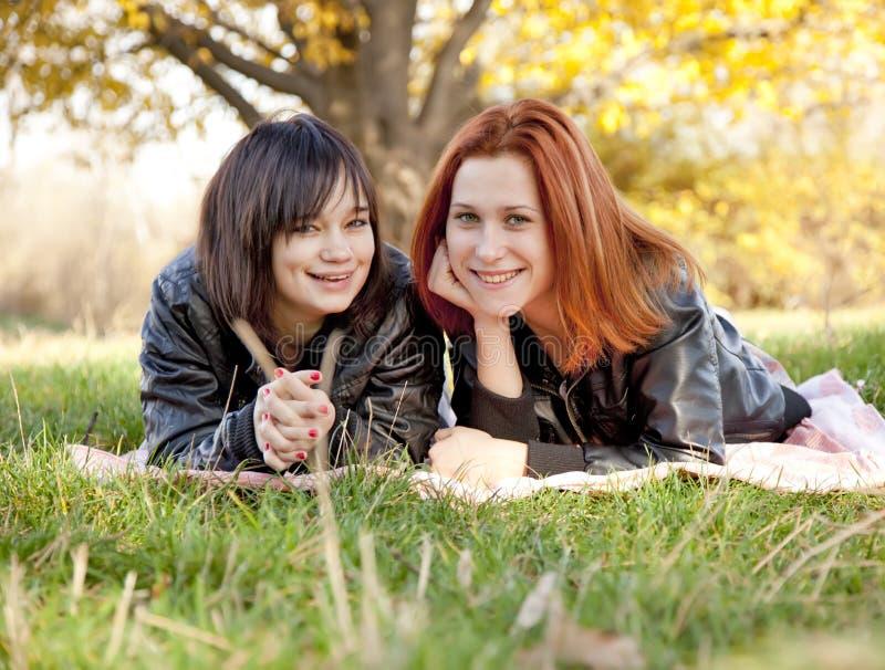 Zwei schöne Freundinnen am Herbstpark stockfoto