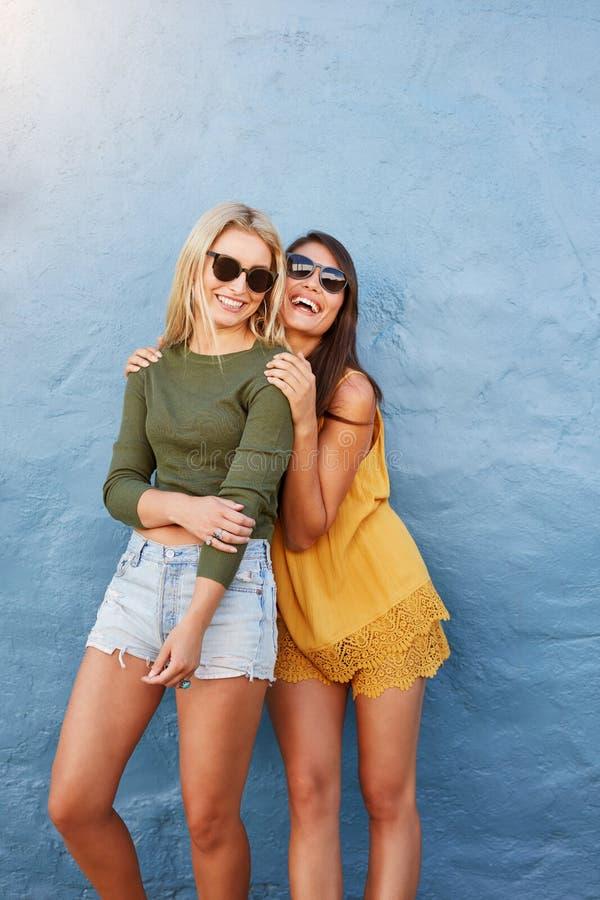 Zwei schöne glückliche Freunde in der Sonnenbrille stockfotografie