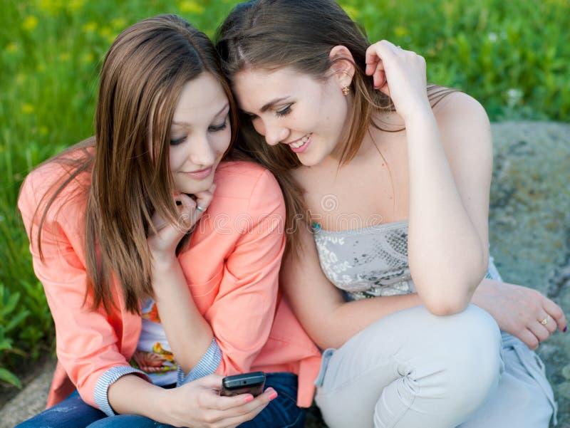 Zwei schöne glückliche junge Frauen u. Handy stockbilder