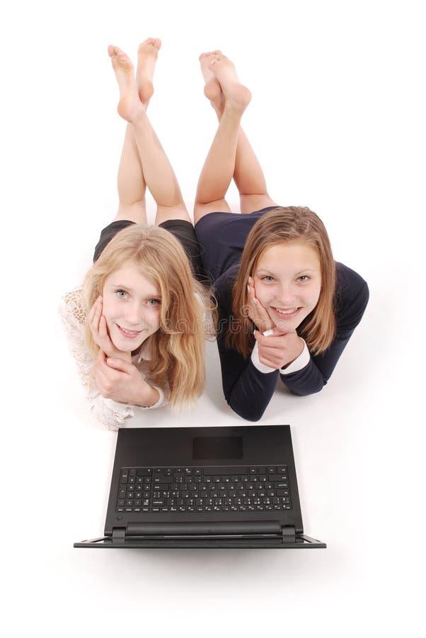 Zwei schöne Jugendlichen, die auf Boden und surfendem Internet auf Laptop liegen stockfoto