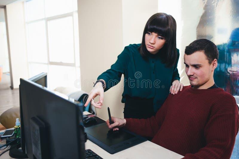 Zwei schöne junge Büroangestellte, die einen Computer betrachten, überwachen und besprechen das Projekt Die Situation im Büro stockfoto