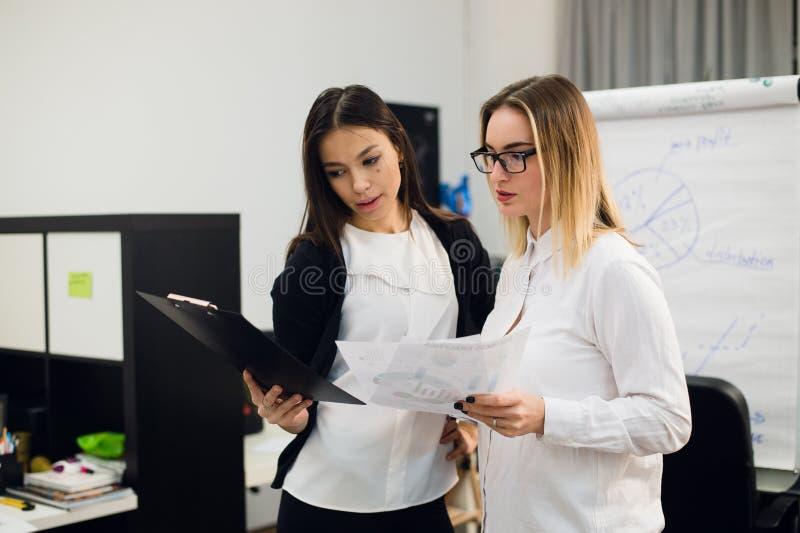Zwei schöne junge Führungskräfte, die etwas Papiere lesen lizenzfreie stockfotografie