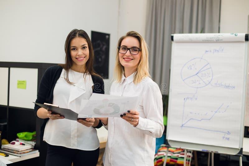 Zwei schöne junge Führungskräfte, die etwas Papiere lesen stockbild