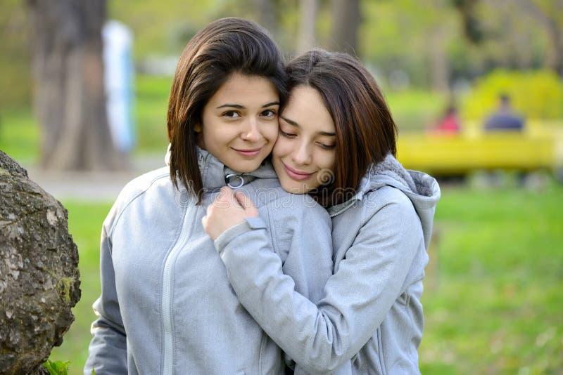 Zwei schöne junge Frauen, die draußen umarmen lizenzfreies stockfoto