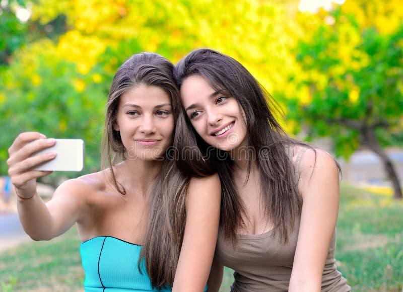 Zwei schöne junge Frauen, die Foto machen stockbild