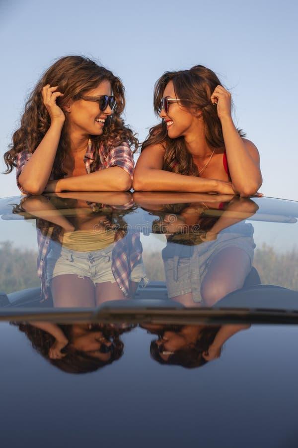 Zwei schöne junge Frauen in einem Kabriolett, das einander betrachtet lizenzfreie stockfotografie