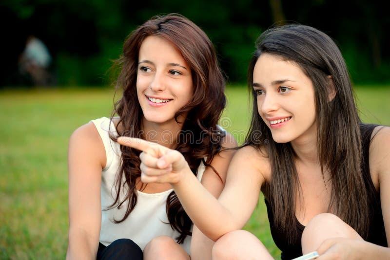 Zwei schöne junge Frauen in einem Parkzeigen lizenzfreie stockbilder