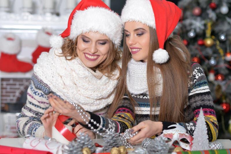 Zwei schöne junge Frauen in Sankt-Hüten, die für Weihnachten sich vorbereiten lizenzfreies stockfoto