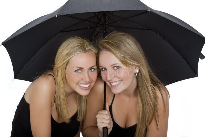 Zwei schöne junge Frauen unter einem Regenschirm lizenzfreie stockfotografie