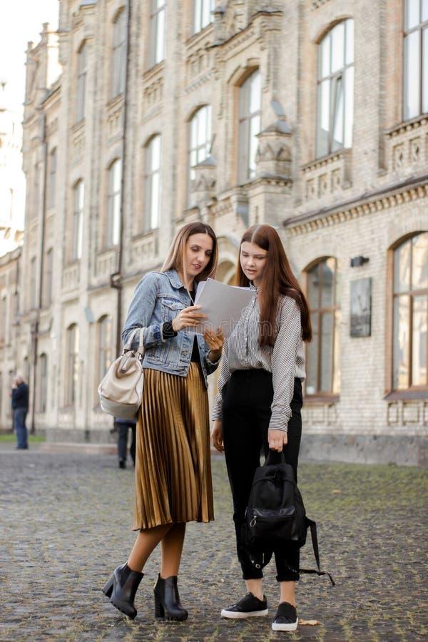 Zwei schöne junge Freunde stehen nahe der Universität und dem Blick am Papier lizenzfreie stockfotos