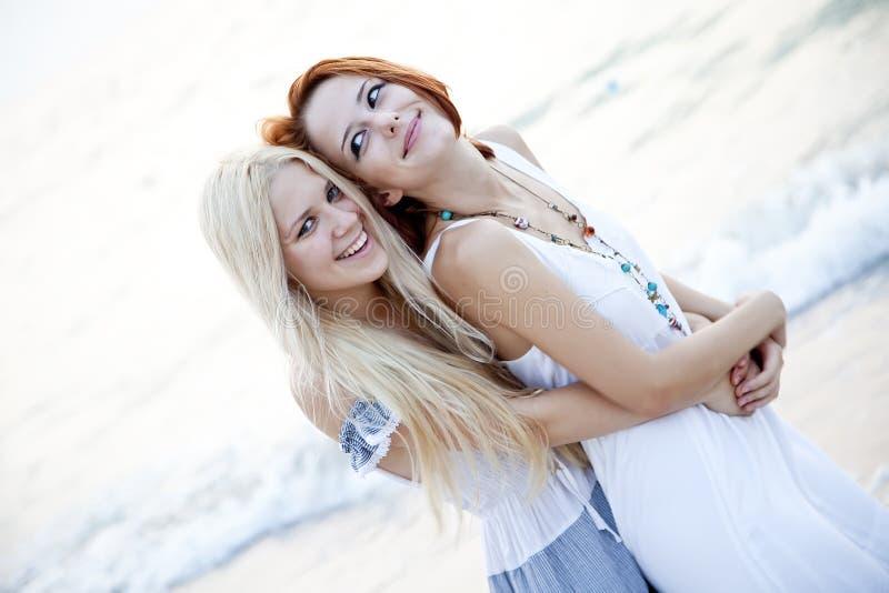 Zwei schöne junge Freundinnen auf dem Strand lizenzfreie stockbilder