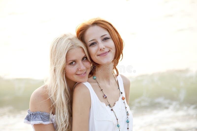 Zwei schöne junge Freundinnen auf dem Strand lizenzfreie stockfotos