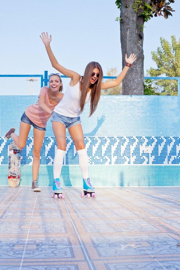 Zwei schöne junge Mädchen auf dem Boden eines leeren Pools lizenzfreies stockbild