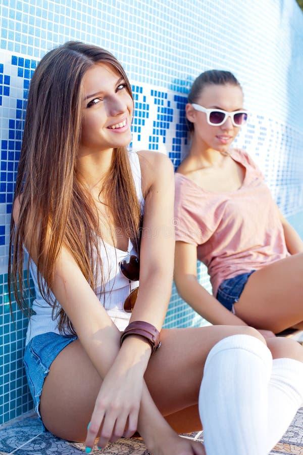 Zwei schöne junge Mädchen auf dem Boden eines leeren Pools stockfotografie