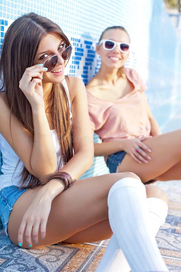 Zwei schöne junge Mädchen auf dem Boden eines leeren Pools lizenzfreie stockbilder